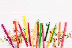 Bunte Bleistifte und Filzstifte, Büroklammern, Briefpapiernägel, smilie Mappen auf weißem hölzernem Hintergrund Lizenzfreies Stockbild