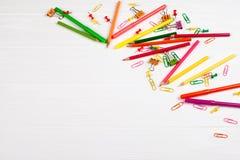 Bunte Bleistifte und Filzstifte, Büroklammern, Briefpapiernägel, smilie Mappen auf weißem hölzernem Hintergrund Stockfoto