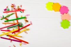 Bunte Bleistifte und Filzstifte, Farbbriefpapier, Büroklammern, Briefpapiernägel auf weißem hölzernem Hintergrund Stockfotos
