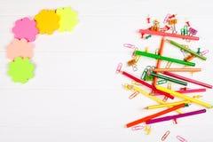 Bunte Bleistifte und Filzstifte, Farbbriefpapier, Büroklammern, Briefpapiernägel auf weißem hölzernem Hintergrund Lizenzfreie Stockfotografie
