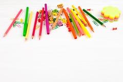 Bunte Bleistifte und Filzstifte, Farbbriefpapier, Büroklammern, Briefpapiernägel auf weißem hölzernem Hintergrund Stockfotografie