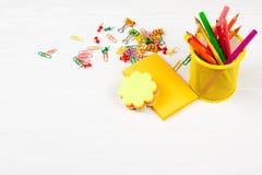 Bunte Bleistifte und Filzstifte im gelben Bleistiftkasten, im bunten Briefpapier, in den Büroklammern und in den Briefpapiernägel Stockbilder