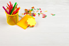 Bunte Bleistifte und Filzstifte im gelben Bleistiftkasten, im bunten Briefpapier, in den Büroklammern und in den Briefpapiernägel Stockbild