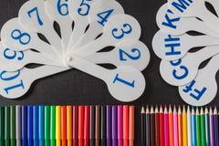 Bunte Bleistifte und Karten von Ziffern und Buchstaben des Alphabetes auf der Tafel Lizenzfreie Stockfotos