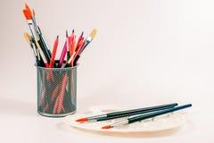 Bunte Bleistifte und Kunstpalette mit Bürsten in einer Schale Stockbilder