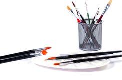 Bunte Bleistifte und Kunstpalette mit Bürsten in einer Schale Lizenzfreie Stockbilder