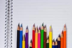 Bunte Bleistifte und leeres Papier auf altem Schreibtisch Stockfoto