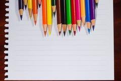 Bunte Bleistifte und leeres Papier auf altem Schreibtisch Lizenzfreie Stockfotos