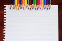 Bunte Bleistifte und leeres Papier auf altem Schreibtisch Lizenzfreie Stockbilder