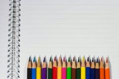 Bunte Bleistifte und leeres Papier auf altem Schreibtisch Stockbilder