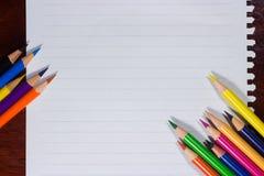 Bunte Bleistifte und leeres Papier auf altem Schreibtisch Stockbild