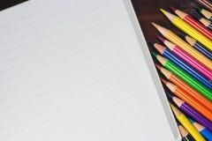 Bunte Bleistifte und leeres Papier auf altem Schreibtisch Lizenzfreies Stockfoto