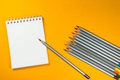Bunte Bleistifte und Notizblock Stockfotos