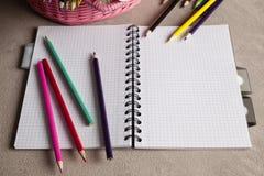Bunte Bleistifte und Notizbuch auf Tabelle Lizenzfreie Stockfotografie