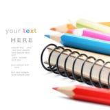 Bunte Bleistifte und Notizbuch getrennt über Weiß Lizenzfreies Stockbild