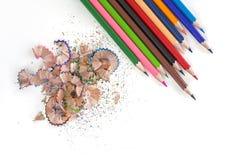 Bunte Bleistifte und Schnitzel auf weißem Hintergrund Lizenzfreie Stockfotografie