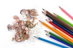 Bunte Bleistifte und Schnitzel auf weißem Hintergrund Lizenzfreie Stockfotos