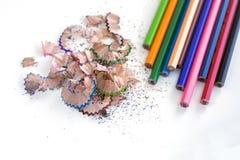 Bunte Bleistifte und Schnitzel auf weißem Hintergrund Stockbild