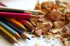 Bunte Bleistifte und Schnitzel vom Schärfen von Bleistiften Bunter Schnitzelhintergrund Lizenzfreie Stockbilder