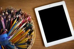 Bunte Bleistifte und Tablet-Computer Stockbilder