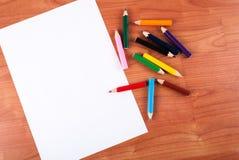 Bunte Bleistifte und weißes leeres Papier auf hölzernem Schreibtisch Lizenzfreies Stockfoto