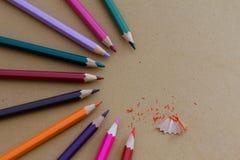 Bunte Bleistifte vereinbarten im halb Kreismuster mit Bleistiftschnitzeln Stockfotos