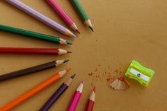 Bunte Bleistifte vereinbarten im halb Kreismuster mit Bleistiftschnitzeln und gelbem Bleistiftspitzer Lizenzfreie Stockbilder
