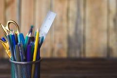 Bunte Bleistifte von violettem gelbem grauem Grünem und blau in der stationären Schale auf Holztisch und Hintergrund Copyspace Lizenzfreie Stockfotos