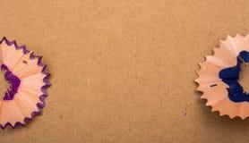 Bunte Bleistiftschnitzel auf braunem Hintergrund Lizenzfreie Stockfotografie
