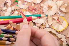 Bunte Bleistiftschnitzel in der Hand Lizenzfreie Stockbilder