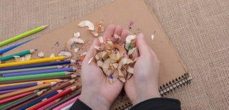 Bunte Bleistiftschnitzel in der Hand Stockfotografie