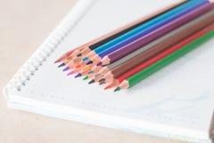 Bunte Bleistiftzeichenstifte der Nahaufnahme auf gewundenem Notizbuch Stockbilder