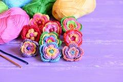 Bunte Blumen der Häkelarbeit eingestellt Häkeln Sie Blumenverzierungen, Baumwollgarn, Haken auf einem hölzernen Hintergrund mit K lizenzfreie stockfotos