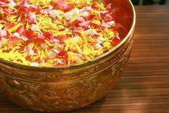 Bunte Blumenblätter, die auf Wasser in der goldenen Schüssel für das Gießen auf die respektierten Hand der Person in Songkran-Fes stockfotos