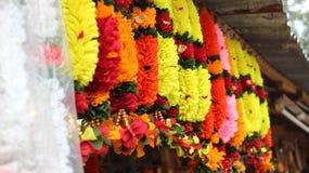 Bunte Blumengirlanden, die am Straßenshop hängen Lizenzfreie Stockfotografie