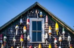 Bunte Bojen, die außerhalb eines kleinen Shops in Maine hängen Stockfotos