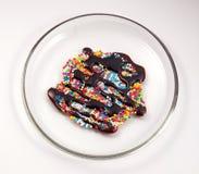 Bunte Bonbons mit Schokoladensoße Stockfotografie