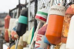 Bunte Boots-Fender, die von einem Zaun hängen Lizenzfreies Stockbild