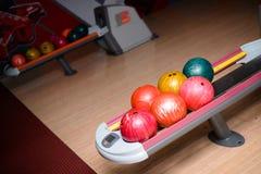 Bunte Bowlingkugeln, die in der Ballrückkehr sitzen Lizenzfreies Stockbild