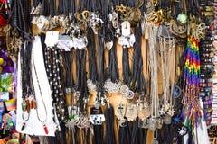 Bunte bracesles und Halskettenbeschaffenheit Handgemachte Juwelen auf der Wand lizenzfreie stockbilder