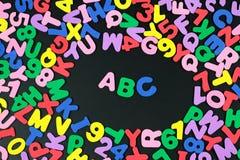 Bunte Buchstaben und Zahlen auf schwarzem Hintergrund Lizenzfreie Stockfotos