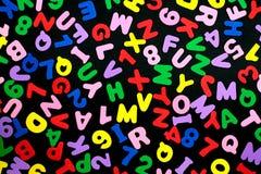 Bunte Buchstaben und Zahlen auf schwarzem Hintergrund Lizenzfreies Stockbild