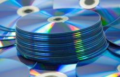 bunte CDs stellten von DVD ein, das auf eine Tabelle zerstreut wurde Lizenzfreie Stockbilder