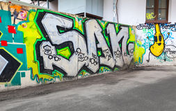 Bunte chaotische Graffiti gemalt über altem Zaun Stockfotos
