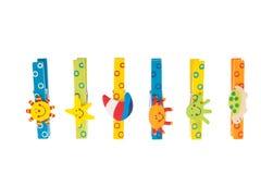 Bunte Clothespins mit hölzernen Abbildungen Stockfotos
