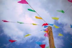 Bunte Dekorationsflaggen gegen Hintergrund des blauen Himmels auf den glücklichen und frohen spielenden Kindern eines Sommerfesti Lizenzfreie Stockbilder