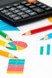 Bunte Diagramme mit Bleistiften und Taschenrechner Lizenzfreie Stockfotografie