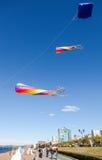 Bunte Drachen, die gegen einen blauen Himmel auf dem Stadtdamm fliegen Stockfotos