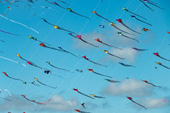 Bunte dreieckige Drachen füllen den blauen Himmel stockfotos