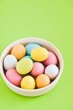 Bunte Eier auf einem weißen Platten- und Grünhintergrund Lizenzfreies Stockfoto